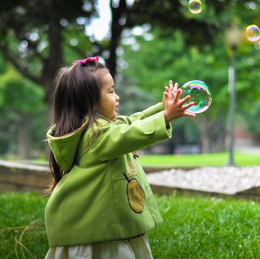Image of young girl chasing a bubble  from The Compounding Lab in Dayton, Ohio website.