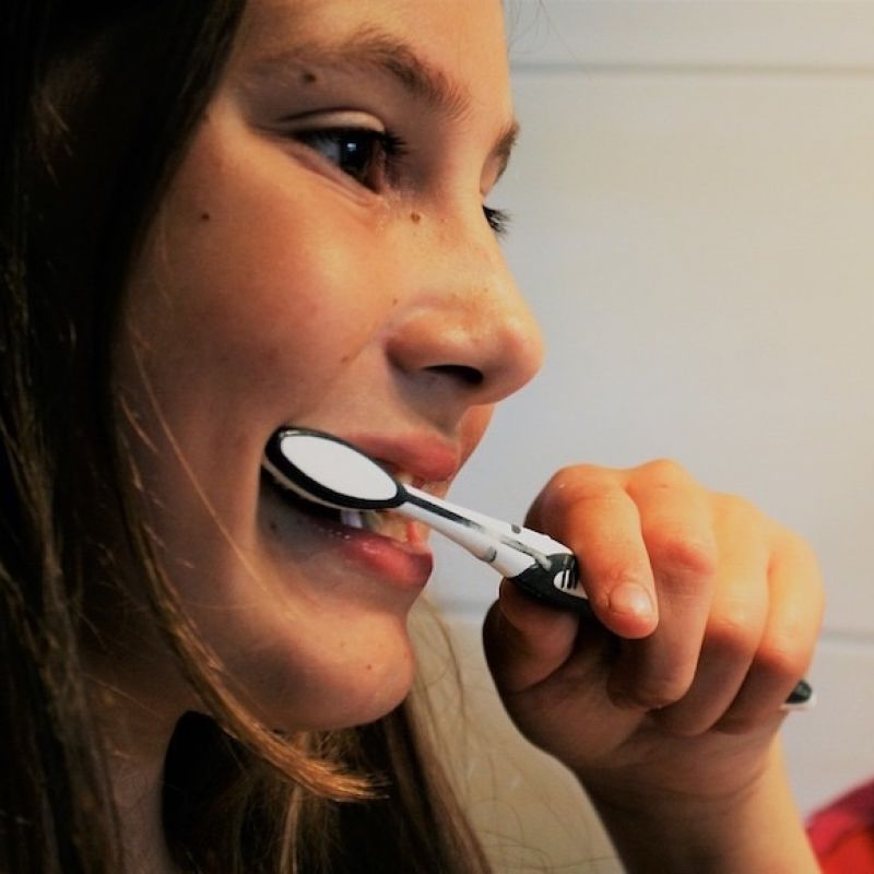 Image of girl brushing teeth from The Compounding Lab in Dayton, Ohio website.